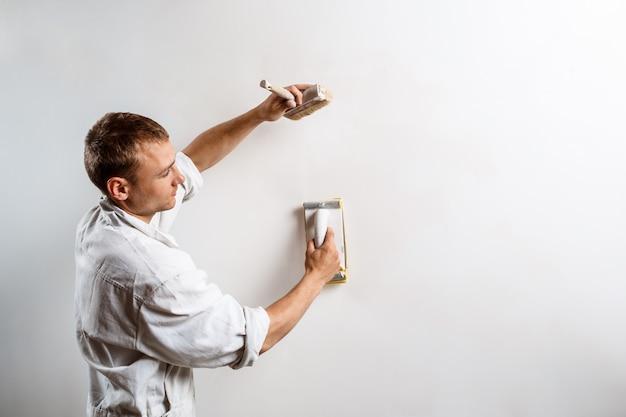Arbeider die witte muur met schuurpapier malen.