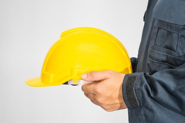 Arbeider die zich in overall bevindt die een bouwvakker houdt