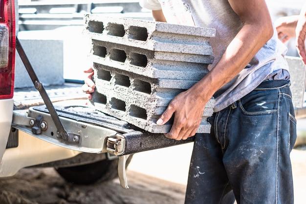 Arbeider die zware bouwmaterialen van de pick-up van de boomstamauto verplaatsen.