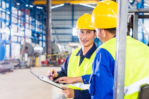 Arbeider en heftruckchauffeur in industriële fabriek