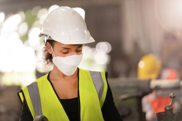 Arbeider fabrieksmensen die gezichtsmasker en veiligheidspak dragen. vrouwen die in de fabriek werken.
