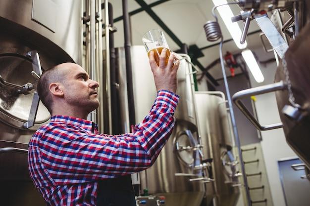 Arbeider het inspecteren bier in glascontainer