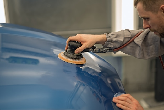 Arbeider in de schilderwinkel van een autocarrosserie, geschilderde voorwerpen schuren
