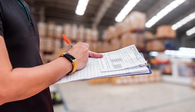 Arbeider in fabriek, checklist in het magazijn