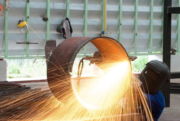 Arbeider in fabriek die staalpijp snijdt die metaaltoorts met behulp van
