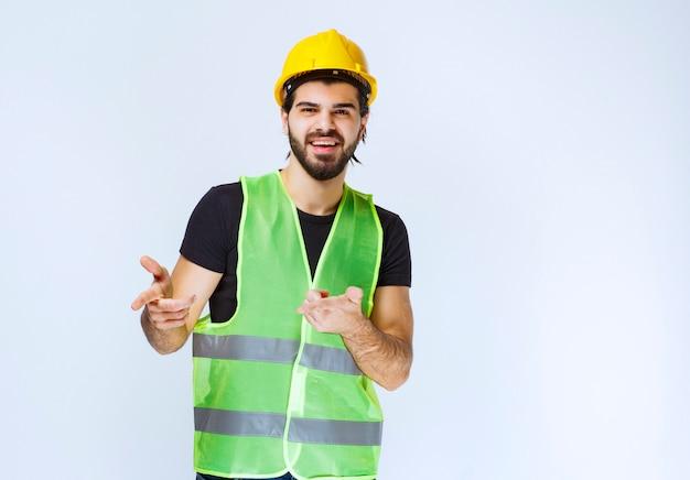Arbeider in gele helm die de persoon vooruit opmerkt.