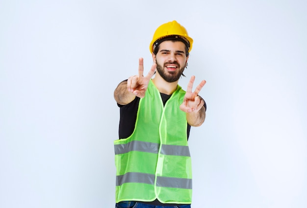 Arbeider in gele helm die vredesteken toont.