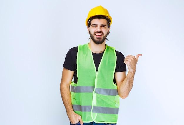 Arbeider in gele helm en uitrusting die erachter wijst.