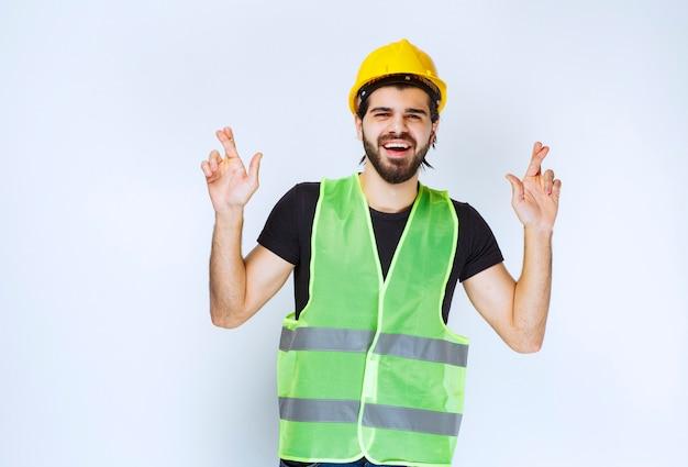 Arbeider in helm die vingerkruis tonen.