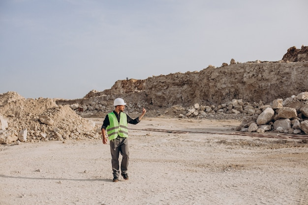 Arbeider in veiligheidshelm die zich in zandgroeve bevindt