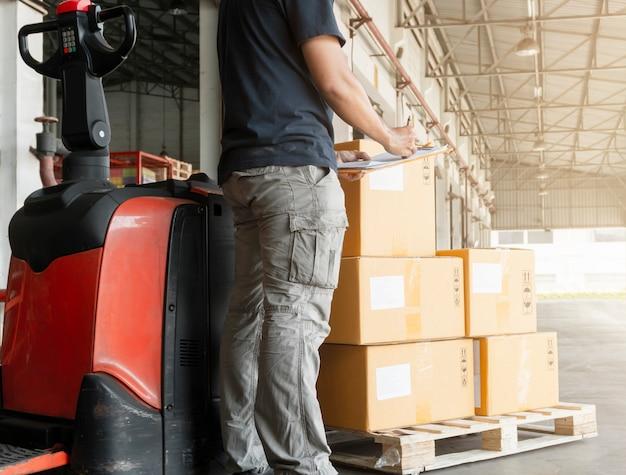 Arbeider-koerier die klembord houdt dat op controlelijst schrijft voor het leveren van palletgoederen, pakketdozen, verpakking, vrachtexport, de logistiek van het industriële pakhuis.