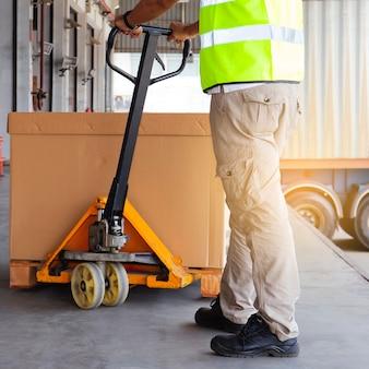 Arbeider met handpallettruck die de verzendingsgoederen aan een vrachtwagen leegmaakt