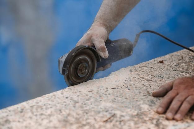 Arbeider met radiale zaag met stof op de lucht met blauwe achtergrond