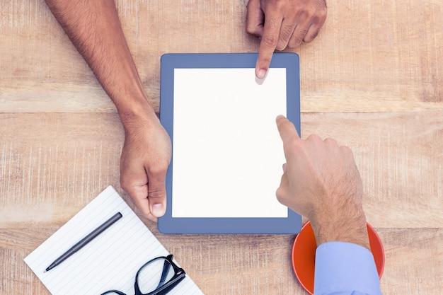 Arbeider onderwijzen andere werknemer iets op de tablet