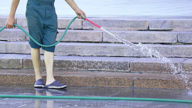 Arbeider van een slang die de stadsstraat water geeft