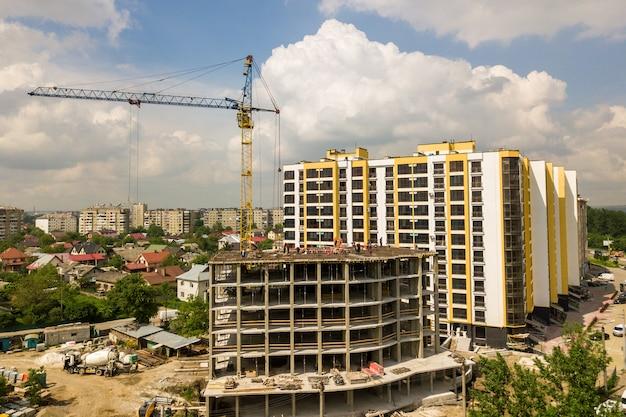 Arbeiders die aan concreet kader van lang flatgebouw in aanbouw in een stad werken.