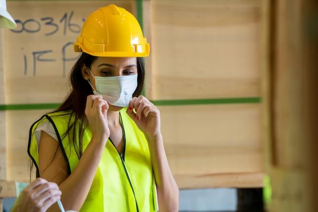 Arbeiders die beschermend masker dragen die bij pakhuis werken.