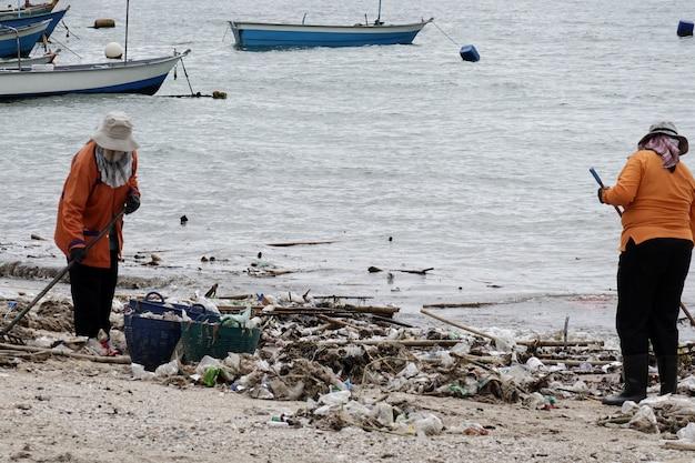 Arbeiders die strand van vuilnis schoonmaken.