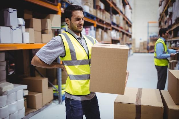 Arbeiders dragende doos in pakhuis met rugpijn