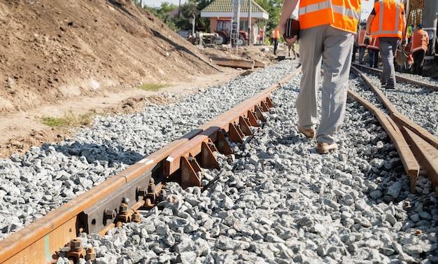 Arbeiders in uniform veranderen de oude spoorlijn