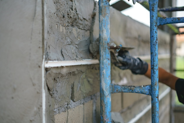 Arbeidersarbeid bouwmuur en upvc-groeilijn met pleistercement