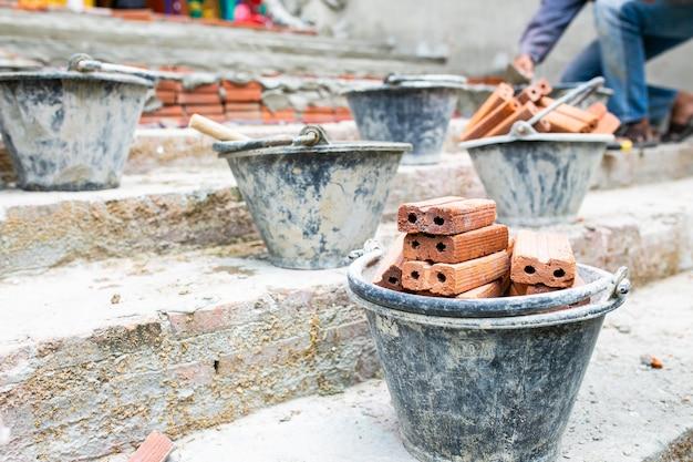 Arbeidersarbeid, mixeroperator het bouwen van trap met betoncement en baksteen bij bouwwerf.