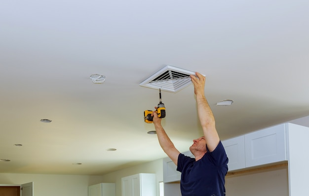 Arbeidersbouwer die de geventileerde bouw van de ventilatiedekking van de bouw installeren