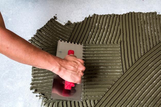 Arbeidershand met troffelhulpmiddel voor tegelsinstallatie die mortel lijm op vloer maken