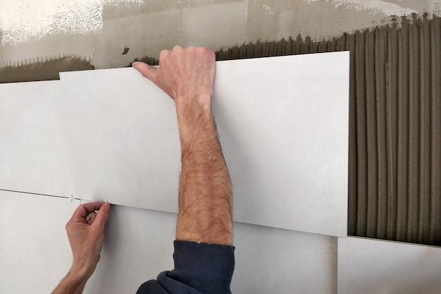 Arbeidershanden die keramische tegels op de muur zetten.