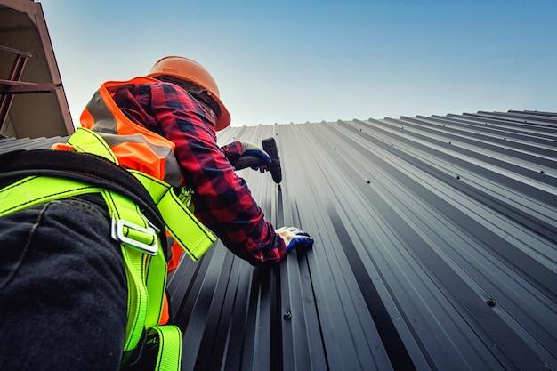 Arbeidersmens die handelaar bouwen op het dak van een huis met veiligheidshelm