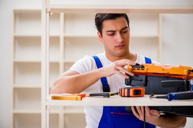Arbeidersmens die het assembleren boekenrek herstellen