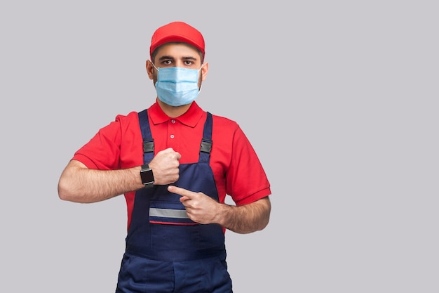 Arbeidersmens in overall die zich tegen grijze achtergrond bevinden