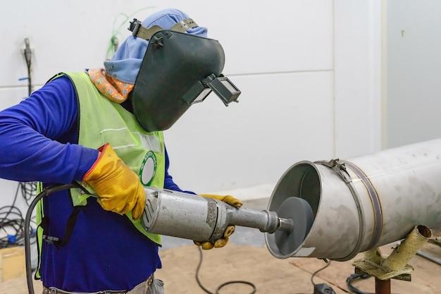 Arbeidersmens met veiligheidsapparatuur die oppervlaktepijp op pijpleiding met een malende machine malen