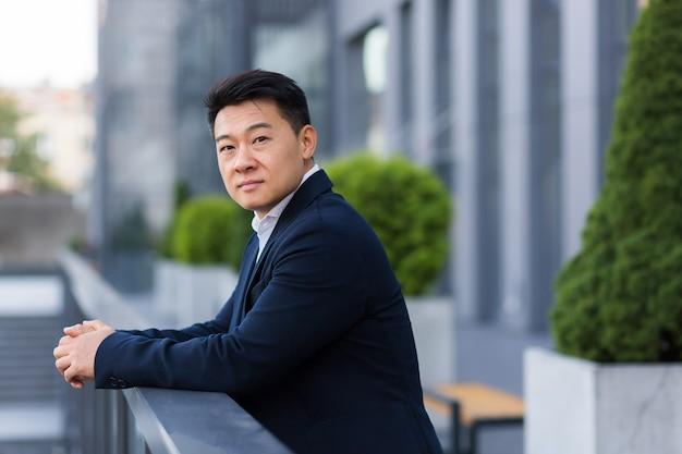 Arbeidersverkoper aziatische zakenman, op het balkon van een modern kantoorcentrum, serieus en zelfverzekerd