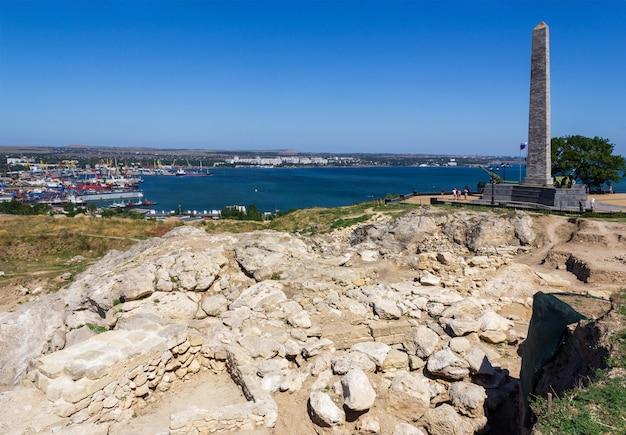 Archeologische opgraving bij de ruïnes van de oude griekse stad panticapaeum met uitzicht op de obelisk of glory voor de onsterfelijke helden op de berg mithridates en de zwarte zee