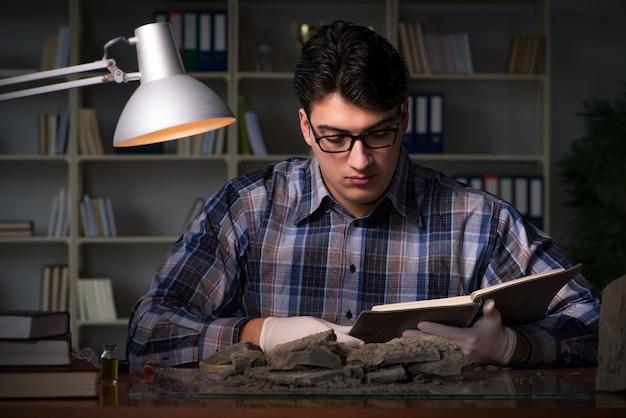 Archeoloog werkt laat in de nacht op kantoor