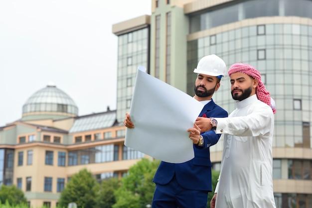 Architect bespreken blauwdrukken met zijn saoedische klant copyspace aan de zijkant