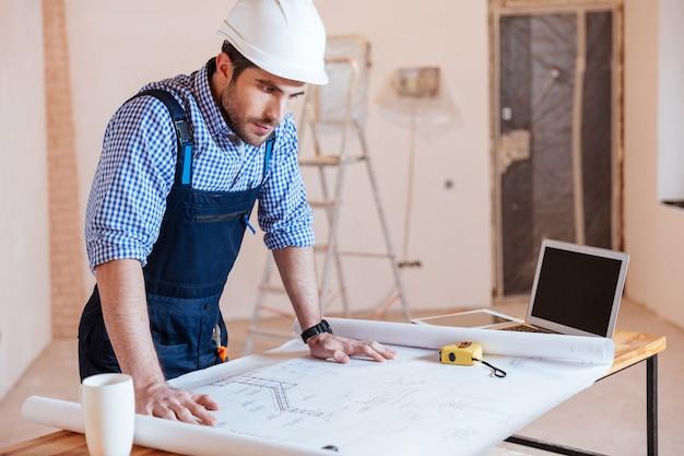 Architect bezig met blauwdruk, grafiek met laptop binnenshuis