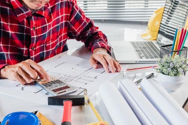 Architect concept. architectenmens die met blauwdrukken op het kantoor werken.