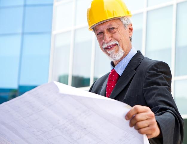 Architect die blauwdruk bekijkt