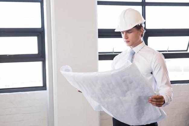 Architect die blauwdruk in bureau bekijkt