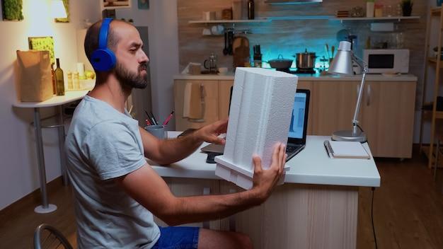 Architect die een bouwmodel vasthoudt terwijl hij 's nachts thuis aan een project werkt. industriële mannelijke werknemer die prototype-idee bestudeert op personal computer die cad-software op het apparaatdisplay toont
