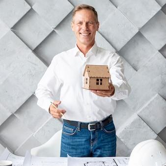 Architect die een miniatuurhuis toont