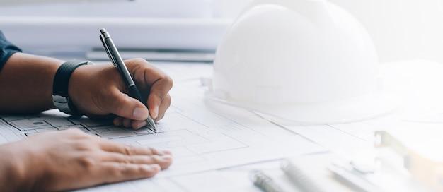 Architect die op een blauwdruk op architecturaal project bij de bouw in het bureau trekt