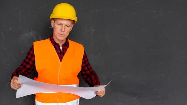 Architect die plannen met exemplaarruimte controleert