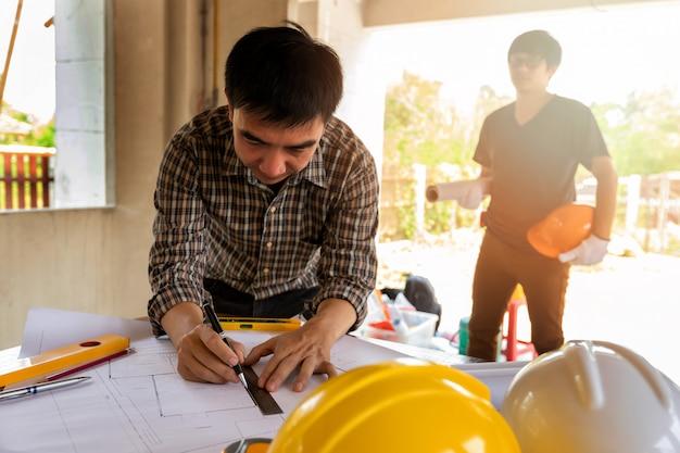 Architect die schaal op blauwdruk in bouwwerf meet.