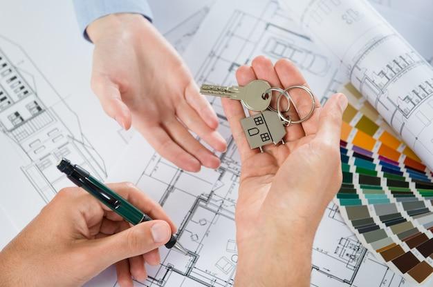 Architect die sleutels overhandigt