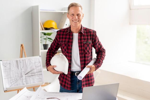 Architect die terwijl het stellen op het kantoor glimlacht