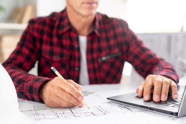 Architect die zijn laptop voor project met behulp van