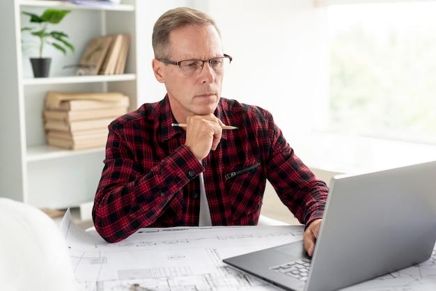 Architect die zijn project op laptop voorbereidt